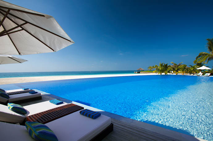 ležaljke ispod suncobrana na bazenu