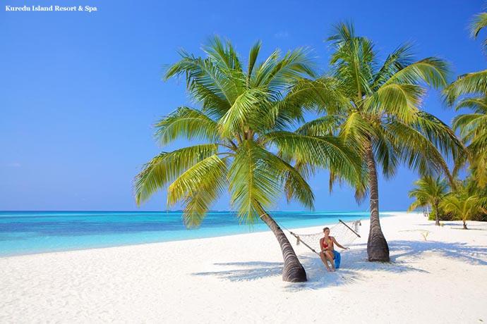 žena na ležaljci između dve palme na plaži