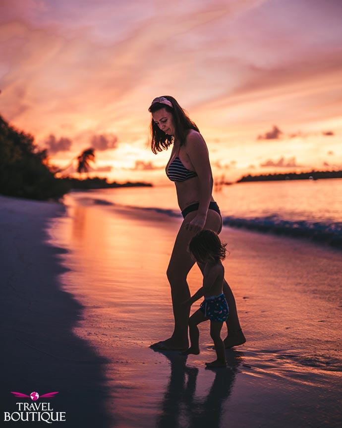 žena i beba na plaži uz zalazak sunca