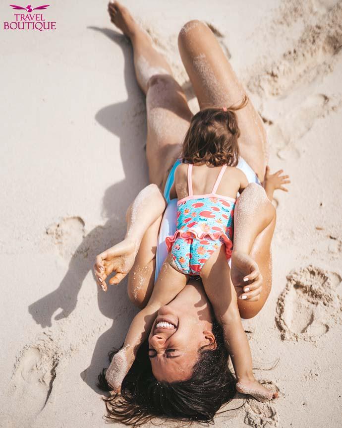 žena i beba se igraju u pesku