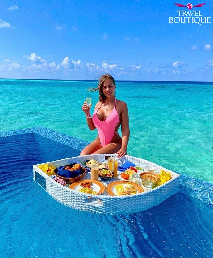 žena sa čašom u ruci sedi na ivici bazena